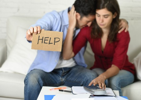 credit crunch: young couple worried need help in stress at home couch accounting debt bills bank papers expenses and payments feeling desperate in bad financial situation
