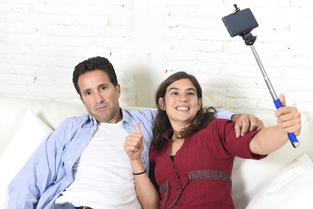 tired face: young attractive couple with woman taking selfie photo or shooting self video with mobile phone and stick and man bored tired and sick of pictures sitting at home  in technology image concept