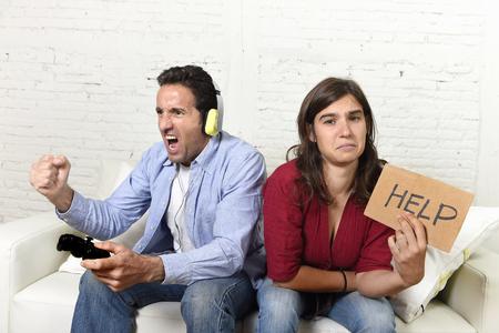 marido y mujer: Mujer atractiva joven que pide ayuda enojado y molesto mientras que el marido o novio juega videojuegos ignorando ella en la tecnología y la adicción a los juegos concepto Foto de archivo
