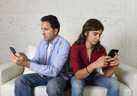 antisocial: young attractive antisocial couple of man and woman together at home couch back to back ignoring each other using mobile phone compulsively in internet communication and social network addiction concept
