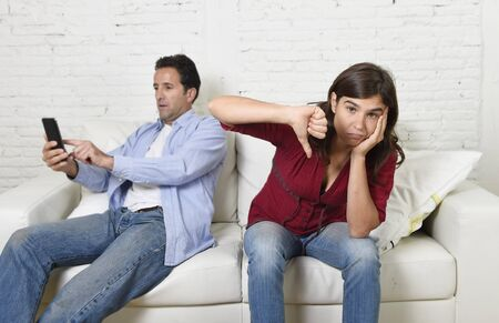 overuse: internet addict man using compulsively mobile phone ignoring wife or girlfriend upset and angry feeling alone in social network addiction and on line communication abuse concept