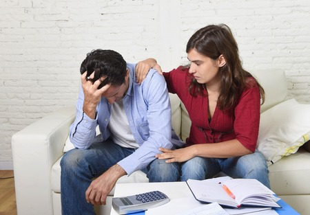 bill payment: young couple worried home in stress wife comforting husband accounting debt unpaid bills bank papers expenses and pending payments feeling desperate in bad financial situation