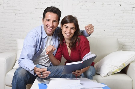 home expenses: young attractive couple accounting at home couch with bank papers and documents, calculator and credit card living cost and mortgage expenses smiling happy in financial success and wealth