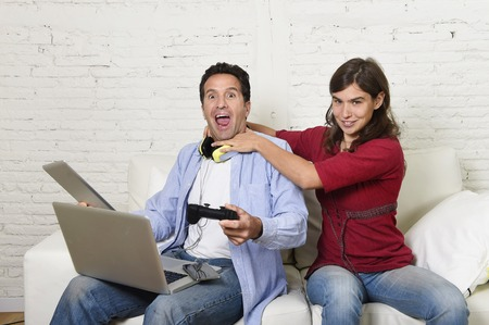 strangling: young attractive frustrated woman strangling technology freak husband or boyfriend for being electronic devices and internet addiction concept Stock Photo