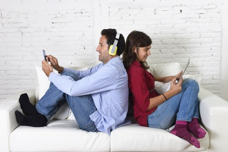 antisocial: young attractive couple sitting on home couch together back to back ignoring each other using mobile phone and digital tablet in social network internet addiction and antisocial behavior concept