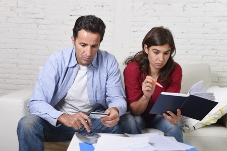 young couple worried home in stress sitting at living room couch accounting debt bills bank papers expenses and payments feeling desperate in bad financial situation Stok Fotoğraf - 46987939
