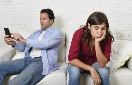 wife: internet addict man using compulsively mobile phone ignoring wife or girlfriend upset and angry feeling alone in social network addiction and on line communication abuse concept