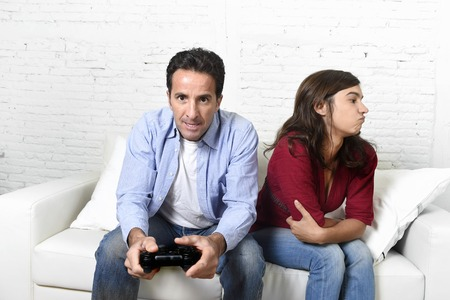 ignoring: young attractive woman bored angry frustrated and upset while husband or boyfriend plays videogames ignoring her in technology and gaming addiction concept Stock Photo