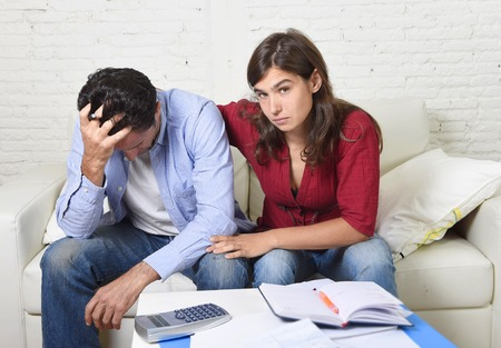 credit crunch: young couple worried home in stress wife comforting husband accounting debt unpaid bills bank papers expenses and pending payments feeling desperate in bad financial situation