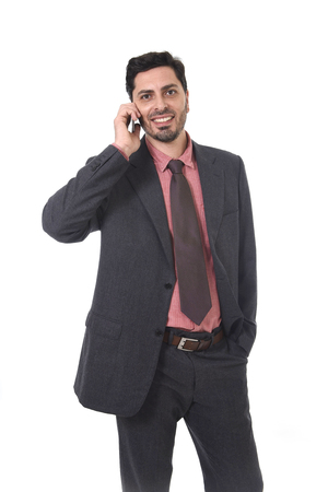brazilian ethnicity: corporate full body portrait of young attractive businessman of Latin Hispanic ethnicity talking on mobile phone in suit and tie standing isolated on white background