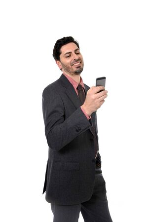 hispanic ethnicity: corporate full body portrait of young attractive businessman of Latin Hispanic ethnicity using mobile phone in suit and tie standing isolated on white background Stock Photo