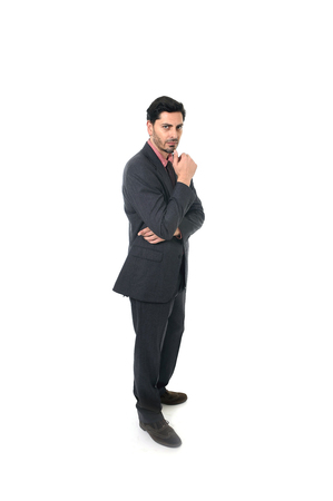 hispanic ethnicity: corporate full body portrait of young attractive businessman of Latin Hispanic ethnicity looking thoughtful in suit and tie standing isolated on white background