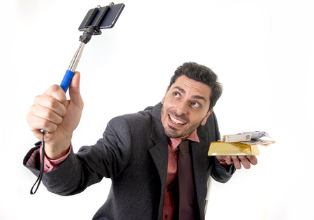 gold bar: young attractive businessman in suit and tie taking selfie photo with mobile phone camera and stick posing happy and successful with gold bar and money  isolated on white background