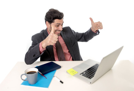 excited: young attractive businessman in suit and tie working happy at office computer laptop looking excited and euphoric in work and business success concept