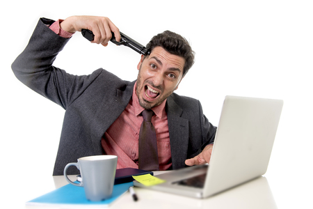 overwork: young businessman in suit and tie sitting at office desk working on computer laptop pointing gun on his tempo in suicide gesture looking sad and depressed in business stress and overwork concept Stock Photo