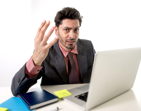 businessman working at his computer: young attractive businessman sitting at office desk working on computer laptop covering his face desperate and worried in work stress and business problems concept