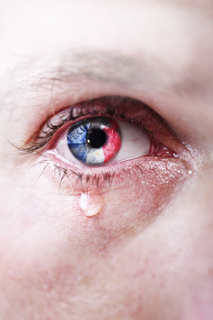 lagrimas: Ascendente cercano del ojo del hombre joven llorando triste llorando con la reflexión francesa bandera en su iris en referencia al ataque terrorista islámica ISIS en París, Francia