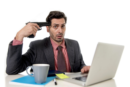 pointing gun: young businessman in suit and tie sitting at office desk working on computer laptop pointing gun on his tempo in suicide gesture looking sad and depressed in business stress and overwork concept Stock Photo