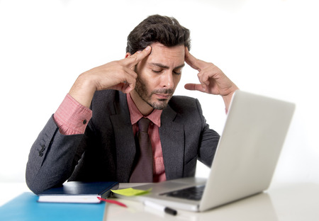 tempo: young attractive businessman sitting at office desk working on computer laptop suffering headache fingers on his tempo looking worried in work stress and business problems concept