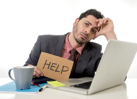 overwork: young businessman in suit and tie sitting at office desk working on computer laptop asking for help holding cardboard sign looking sad and depressed in business stress and overwork concept Stock Photo
