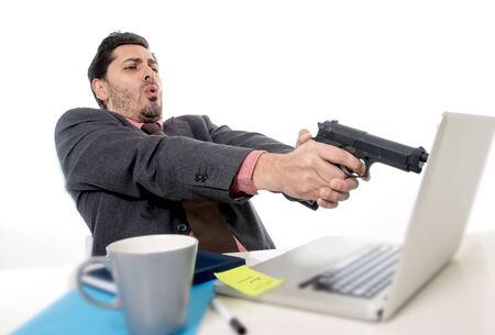 pointing gun: young businessman in suit and tie sitting at office desk working on computer  pointing gun to laptop in business problems stress and overwork concept