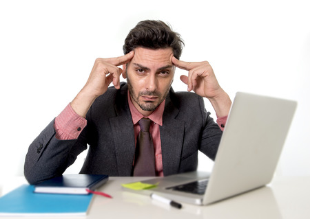 businessman working at his computer: young attractive businessman sitting at office desk working on computer laptop suffering headache fingers on his tempo looking worried in work stress and business problems concept