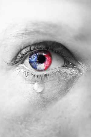 catchlight: Close up eye of young man crying sad in tears with french flag reflection on his iris in reference to ISIS Islamic terrorist attack in Paris France, black and white isolated colour edition Stock Photo