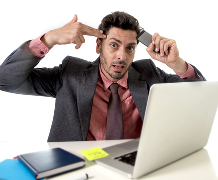tempo: young attractive businessman sitting at office desk working stressed on computer laptop holding mobile phone against his forehead pointing hand in gun sign to his tempo overworked in work stress