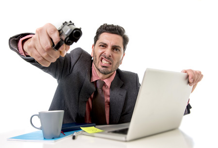 pointing gun: young businessman in suit and tie sitting at office desk working on computer laptop pointing gun looking angry and crazy in business stress and overwork concept