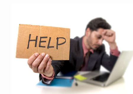 financial issues: young businessman in suit and tie sitting at office desk working on computer laptop asking for help holding cardboard sign looking sad and depressed in business stress and overwork concept Stock Photo