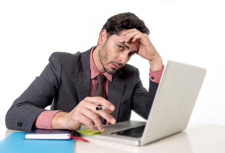 overwork: young attractive businessman in suit and tie sitting at office desk working on computer laptop looking tired and busy in work stress and overwork concept