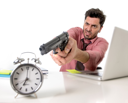 adentro y afuera: joven atractivo hombre de negocios en el estr�s en el ordenador del escritorio de oficina que se�ala el arma de mano con el reloj de alarma en el tiempo y fecha l�mite del proyecto concepto vencimiento en enojado y frustreated expresi�n de la cara Foto de archivo