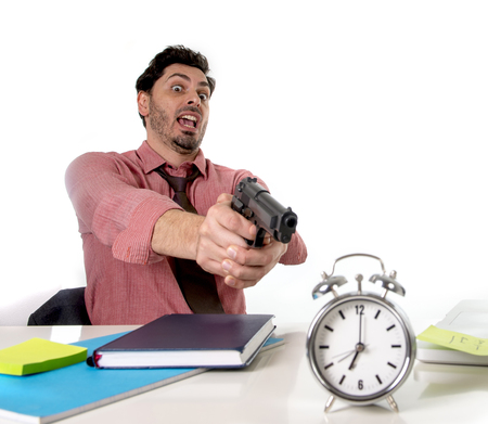 expiring: young attractive businessman in stress at office desk pointing hand gun to alarm clock in out of time and project deadline expiring concept in angry  and frustreated face expression Stock Photo