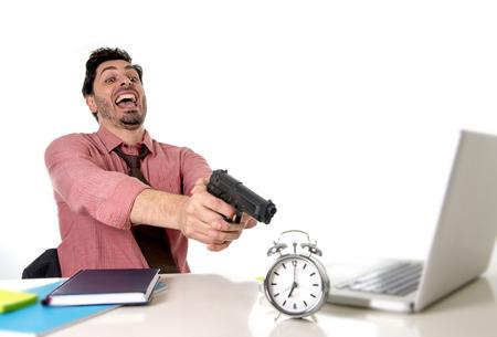 dentro fuera: joven atractivo hombre de negocios en el estr�s en el ordenador del escritorio de oficina que se�ala el arma de mano con el reloj de alarma en el tiempo y fecha l�mite del proyecto concepto vencimiento en enojado y frustreated expresi�n de la cara Foto de archivo