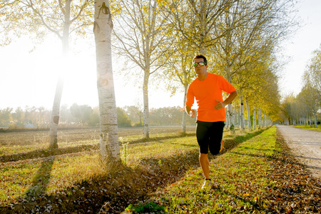 off track: front view of young sport man running outdoors in off road trail track with trees under Autumn sunlight in fitness, countryside training and healthy lifestyle concept