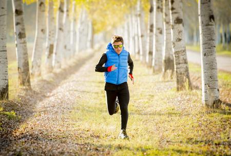 hombre fuerte: Vista frontal Joven corriendo el deporte al aire libre en pista todo terreno carretera con �rboles en la luz del sol de oto�o que llevan a correr chaleco y gafas de sol en la aptitud, entrenamiento campo y el concepto de estilo de vida saludable Foto de archivo