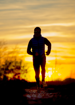 off track: Silhouette front view of young sport man running outdoors in off road trail track with Autumn sun at orange sky sunset as background in training workout  and healthy lifestyle concept