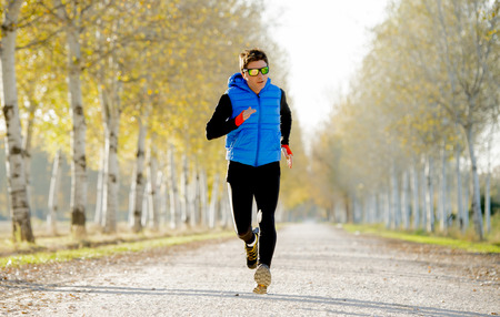 man health: front view young sport man running outdoors in off road trail ground with trees in Autumn sunlight wearing jogging vest and sunglasses in fitness, countryside training and healthy lifestyle concept Stock Photo