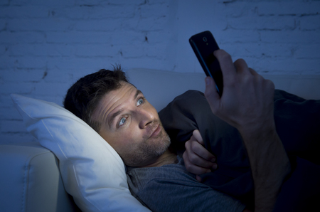 addiction alone: young man in bed couch at home late at night with intense face expression using mobile phone in low light watching online porn enjoying alone in internet addiction