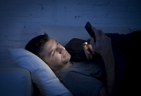 young man in bed couch at home late at night texting on mobile phone in low light relaxed in communication technology and internet social network concept