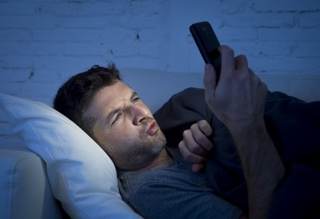 internet porn: young man in bed couch at home late at night with intense face expression using mobile phone in low light watching online porn enjoying alone in internet addiction
