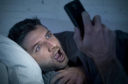buonanotte: giovane uomo a letto divano a casa a tarda notte con intensa espressione del viso con il cellulare in condizioni di scarsa luminosità a guardare porno online godendo solo in dipendenza da Internet