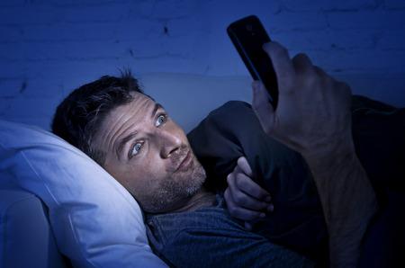 jonge man in bed bank thuis 's avonds laat met een intense gezicht expressie met behulp van de mobiele telefoon bij weinig licht het kijken naar online porno te genieten alleen in Internet verslaving