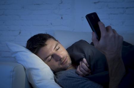 buonanotte: giovane in divano letto a casa addormentarsi a tarda notte, mentre usando il telefono cellulare in condizioni di scarsa luce rilassato nella dipendenza tecnologie di comunicazione e internet concetto di social network