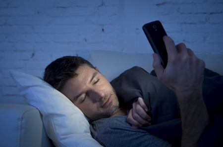 cell phone addiction: young man in bed couch at home falling asleep late at night while using mobile phone in low light relaxed in communication technology addiction and internet social network concept