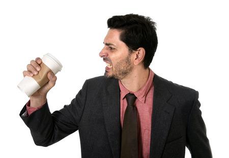 怒っていると強調したビジネスマンのスーツとネクタイは、白い背景で隔離カフェイン中毒の概念で取る離れてコーヒーの空のカップを粉砕