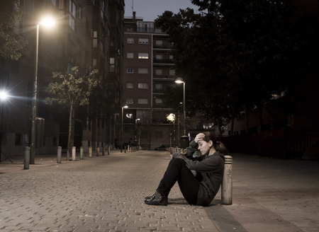 young sad woman sitting on street ground at night alone desperate suffering depression left abandoned and lost in grunge urban background as abuse and violence female victim or addict concept Banco de Imagens