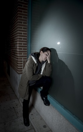 girl portrait: young sad woman alone leaning on street window at night looking desperate suffering depression crying in pain lonely and lost as violence and abuse female victim or addict concept Stock Photo