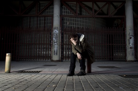 young woman alone on street covering her face suffering depression looking sad desperate and helpless sitting lonely in dirty dark urban night background in female victim of abuse concept