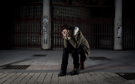 helpless: young woman alone on street covering her face suffering depression looking sad desperate and helpless sitting lonely in dirty dark urban night background in female victim of abuse concept